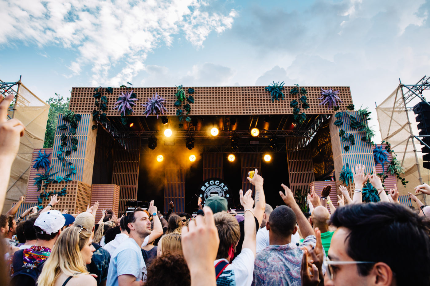 Image of a festival crowd with hands in the air with main stage in the background