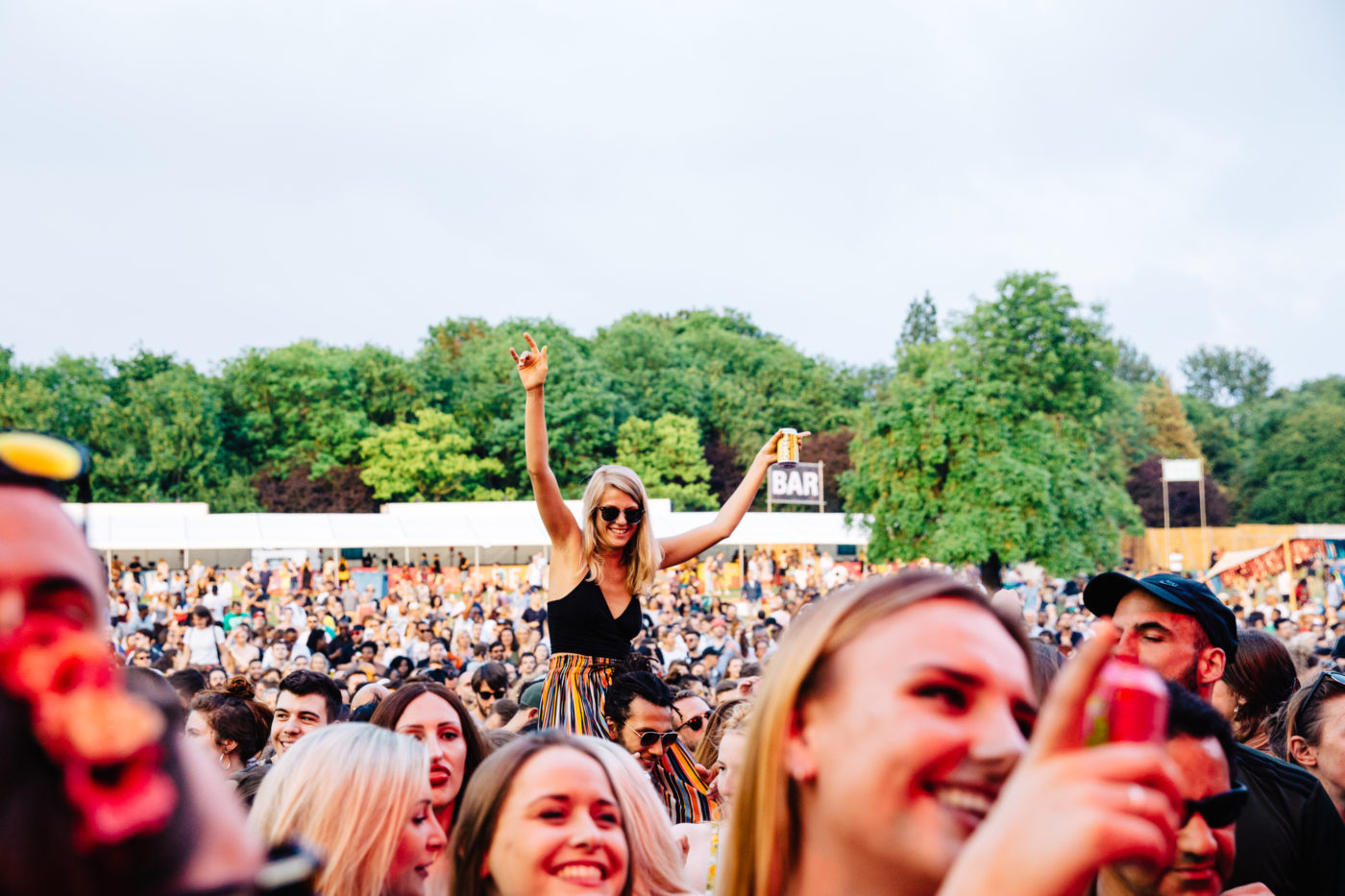 Image of festival crowd with smiling people, in the middle distance is a woman with her arms in the air sitting on someone's shoulders