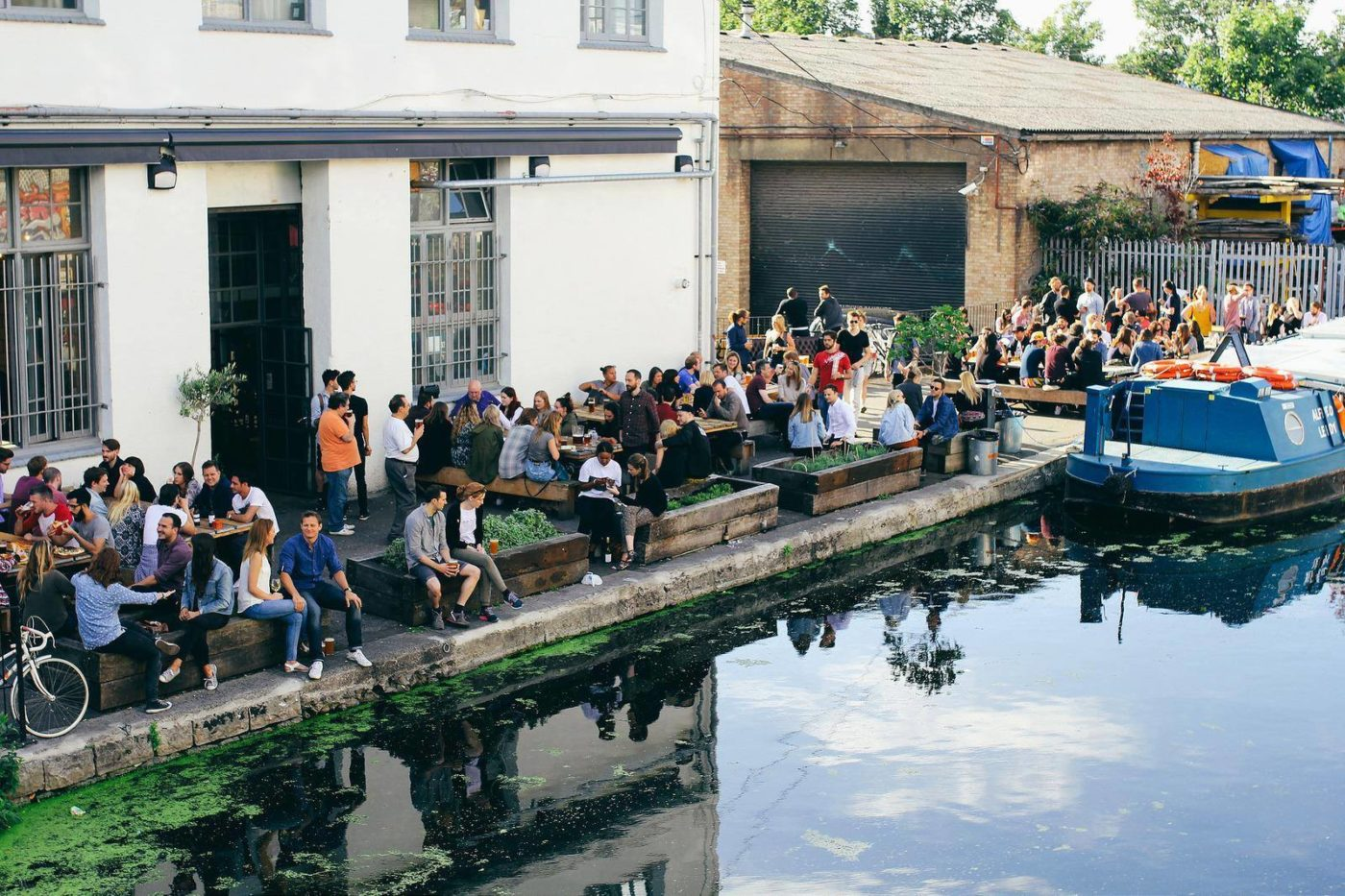 Image of outdoor restaurant or bar scene by Hackney Wick with crowd of people in the sun