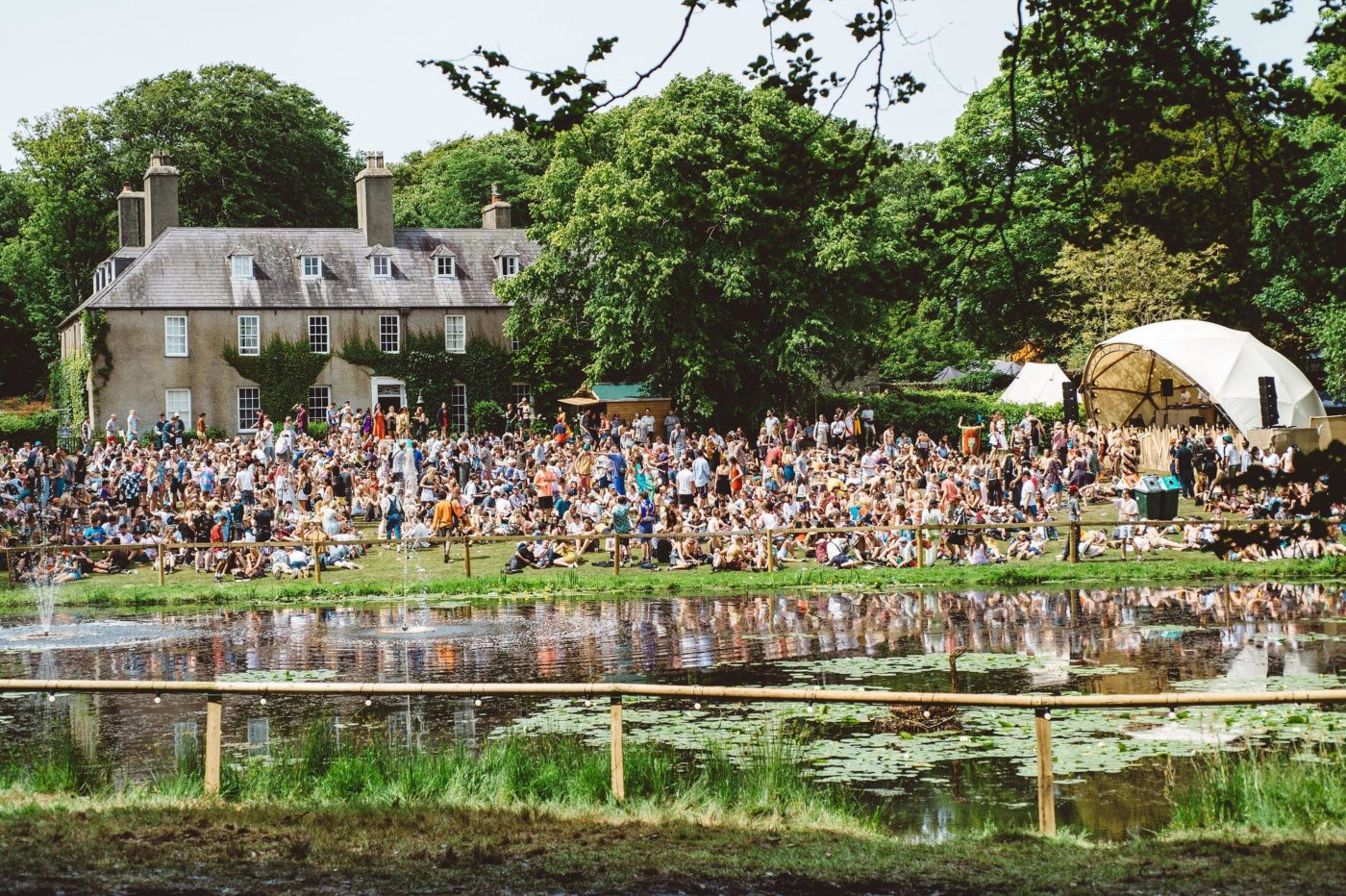 Image of a lake with a large festival crowd in the distance