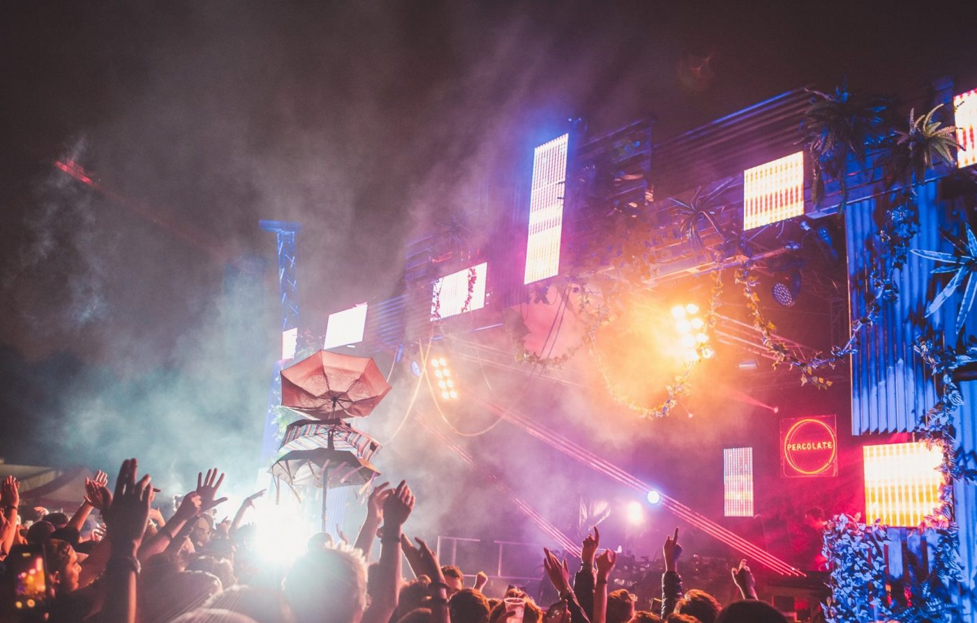 Image of festival crowd at night in front of bright lights and stage