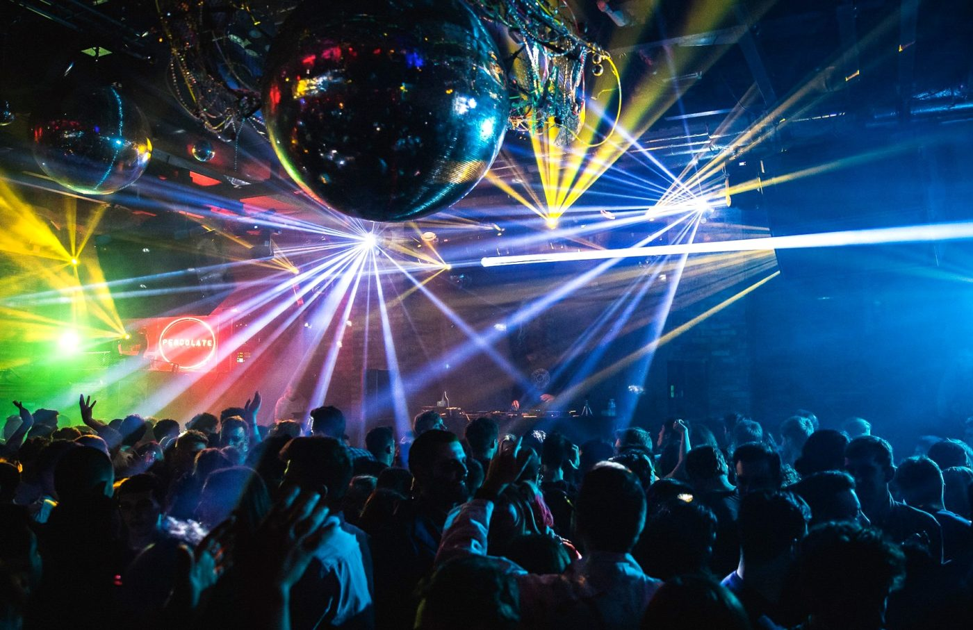 Image of a crowd dancing at a party underneath a large disco ball
