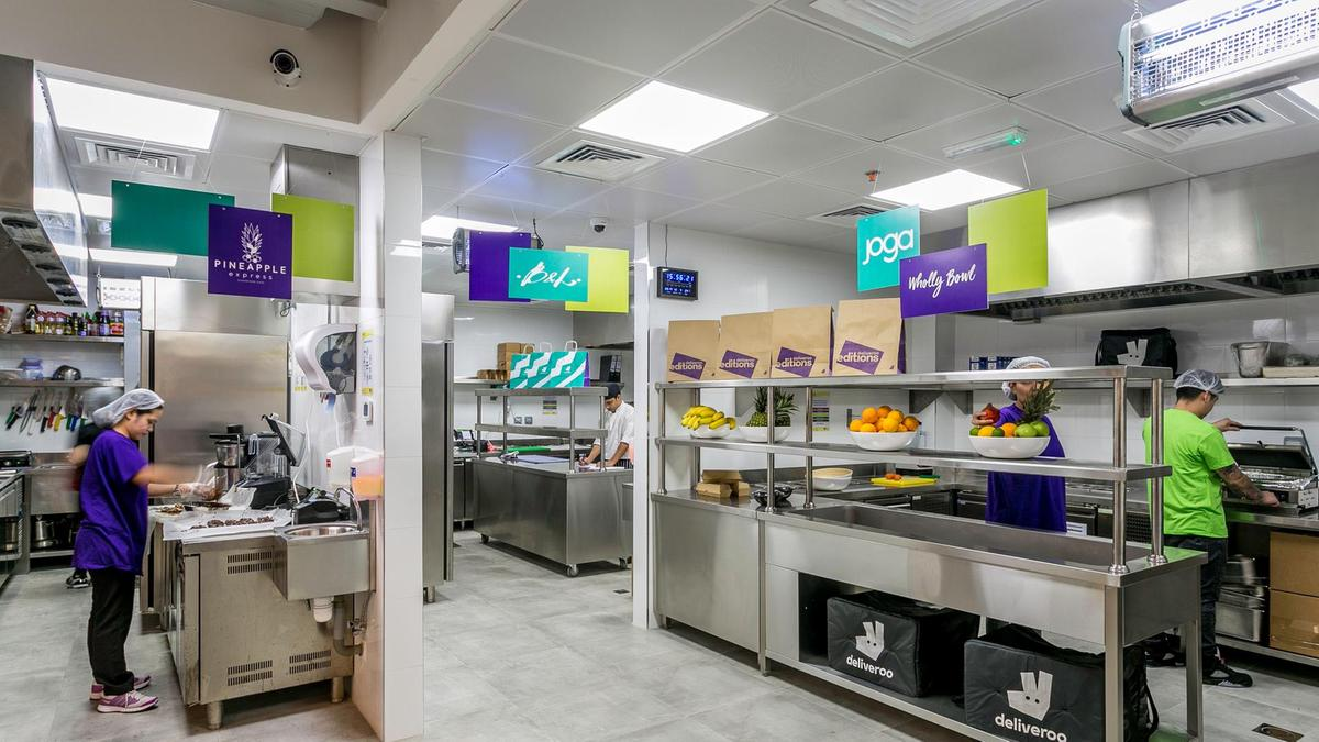 A busy kitchen featuring logos and designs for the brand Deliveroo Editions