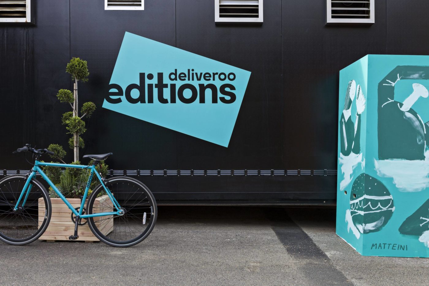 Image of a bicycle in front of a backdrop featuring the creative branding of the startup Deliveroo Editions