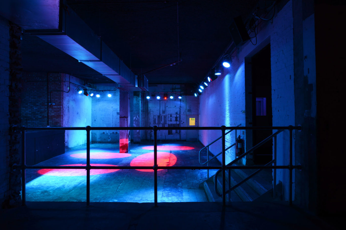 Image of a vacant club space with coloured spotlights